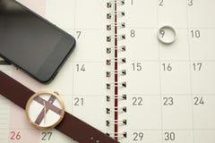 Slimme telefoon, horloge en zilveren ring gezet op Desktopkalender Royalty-vrije Stock Foto's