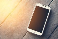 Slimme telefoon op het houten behang als achtergrond Royalty-vrije Stock Foto's