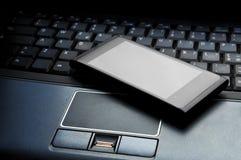 Slimme telefoon op laptop stock afbeeldingen