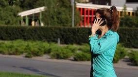 Slimme telefoonvrouw die mobiele telefoon uitnodigen bij park Knappe jonge vrouw die bij smartphone gelukkig glimlachen in openlu stock videobeelden