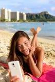 Slimme telefoonvrouw die smartphone app op strand gebruiken royalty-vrije stock afbeeldingen