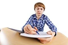 Slimme tienerjongen die voor school leert Stock Foto
