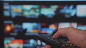 Slimme TV De online video stromende dienst met apps en hand Mannelijke hand die de controledraai houden van slimme TV ver stock footage