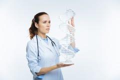 Slimme vrouwelijke arts die DNA-model onderzoeken Royalty-vrije Stock Afbeelding