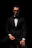 Slimme zakenman in het zwarte stellen in donkere studio die glazen dragen Stock Fotografie