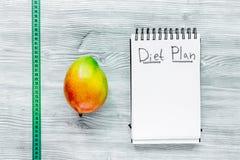 slimming Тетрадь для плана диеты, плодоовощей и измеряя ленты на серой насмешке взгляд сверху деревянного стола вверх Стоковое Изображение RF