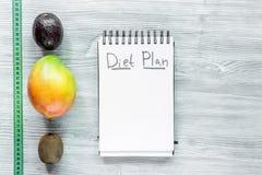 slimming Тетрадь для плана диеты, плодоовощей и измеряя ленты на сером copyspace насмешки взгляд сверху деревянного стола Стоковое Изображение