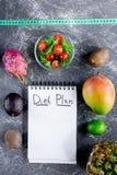 slimming Тетрадь для плана диеты, плодоовощей, салата и измеряя ленты на серой каменной насмешке взгляда столешницы вверх Стоковое фото RF