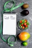 slimming Тетрадь для плана диеты, фруктового салата и измеряя ленты на серой каменной насмешке взгляда столешницы вверх Стоковые Фото