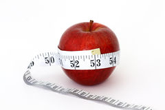 Slimming apple. A red apple with a red measuring tape around it Royalty Free Stock Image