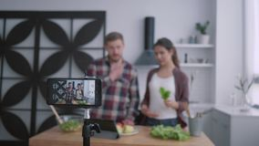 Slimming blog, vloggers male and female prepare healthy brunch with vegetables and greens in cuisine while camera cell stock footage