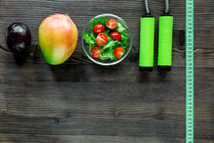 Slimming concept. Fruits, salad, measuring tape and skipping rope on wooden table top view copyspace Royalty Free Stock Photo