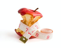 Slimming diet_01. Stub of a red apple wrapped dressmaker meter isolated on a white background Royalty Free Stock Photo