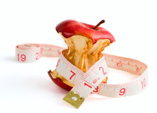 Slimming diet_02. Stub of a red apple wrapped dressmaker meter isolated on a white background Royalty Free Stock Images