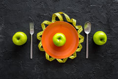 Slimming diet. Apple at plate and measuring tape on black background top view Royalty Free Stock Photography