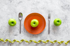 Slimming diet. Apple at plate and measuring tape on grey stone background top view Royalty Free Stock Photo
