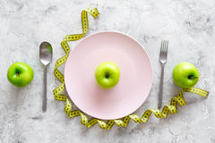 Slimming diet. Apple at plate and measuring tape on grey stone background top view Stock Images