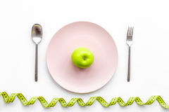 Slimming diet. Apple at plate and measuring tape on white background top view Royalty Free Stock Photos