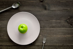 Slimming diet. Apple at plate on wooden background top view copyspace Stock Images