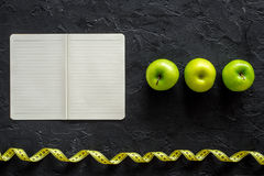 Slimming diet dairy. Notebook, apples and measuring tape on black background top view mockup Royalty Free Stock Photography