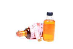 Slimming oils. Beautiful shot of slimming oil bottles with measuring tape Stock Photos