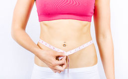 Slimming Woman Holding Tape Measure To Stomach. Woman Holding Tape Measure To Body While Working Out To A Lifestyle Of Diet And Exercise Royalty Free Stock Image