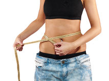 Slimming woman measuring her thigh with measuring tape. Royalty Free Stock Image