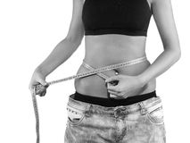 Slimming woman measuring her thigh with measuring tape. Royalty Free Stock Photo