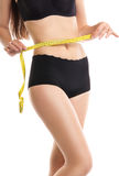 Slimming woman measuring her thigh with waist tape. Stock Photo