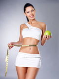 Slimming woman with a measuring tape and apple. Healthy lifestyle for female Stock Image