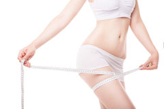 Slimming woman measuring thigh with tape Stock Images