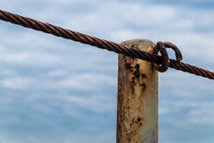 Sling railing. Column with sling railing around a rusty ship on cloudy blue sky background stock images
