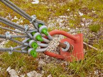 Sling and scrap in green yard, iron twisted rope fixed by screws snap hooks and grommets at anchor in ground. Sling and scrap in green yard, iron twisted rope Royalty Free Stock Image