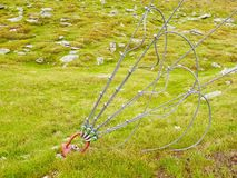 Sling and scrap in green yard, iron twisted rope fixed by screws snap hooks and grommets at anchor in ground. Royalty Free Stock Image