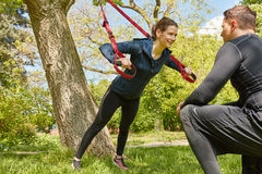 Sling training with Personal Trainer. Woman sling training with Personal Trainer at park Stock Image