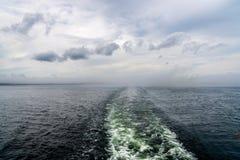 Slinga för vak för kryssningskepp mot disig horisont med moln Royaltyfria Foton