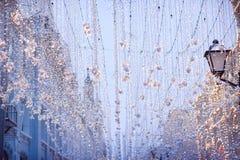 Slingerdecoratie in de Kerstmisvooravond in openlucht op de straat royalty-vrije stock foto's