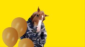 Slingerende mens met een paardhoofd en vliegende gele ballons