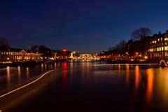 Slingor av ljus på en av de viktiga kanalerna i Amsterdam på natten arkivfoton