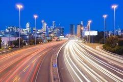 Slingor för snabb trafik och ljusi huvudväg på skymning Arkivfoto