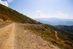 Slingrande berg Grusväg i bergen Landsväg i bergen Arkivfoto