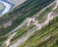 Slingrande väg i dalen av de Altai bergen i sommar arkivbild