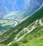 Slingrande väg i dalen av de Altai bergen i sommar arkivfoton