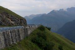 Slingrande väg och härliga moln som är höga i bergen arkivbild