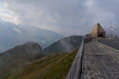 Slingrande väg och härliga moln som är höga i bergen arkivfoton