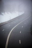 Slingrig huvudväg för vinter i dimma Royaltyfri Fotografi