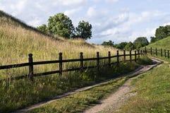 Slingrig landsväg med trästaketet Arkivbild