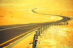 Slingrig svart asfaltväg till och med sanddyerna av den Liwa oasen, Förenade Arabemiraten Royaltyfria Foton