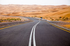 Slingrig svart asfaltväg till och med sanddyerna av den Liwa oasen, Förenade Arabemiraten Royaltyfria Bilder