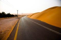 Slingrig svart asfaltväg till och med sanddyerna av den Liwa oasen, Förenade Arabemiraten Arkivbilder